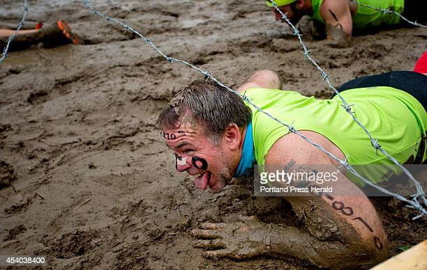 A competitor in the Tough Mudder obstacle course a 103 mile trail run littered with hazards crawls through the 'Kiss the Mud' hazard while competing...