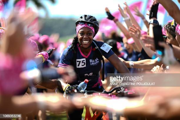 A competitor is cheered on as she crosses the finish in the mountain bike race during the Raid des Alizes an exclusively allfemale multi sport...