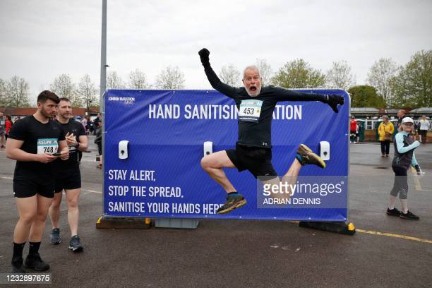 Competitor jumps for a photo in front of the hand sanitiser station ahead of the socially-distanced Reunion 5K running race, one of the pilot events...