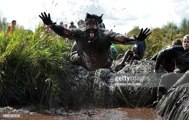 A competitor jumps head first into a mud pool as he takes part in the Mud Madness race at Foymore Lodge on September 13 2015 in Portadown Northern...