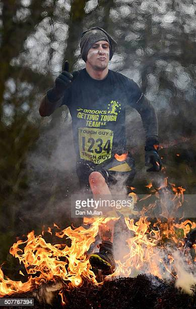 A competitor leaps through a fire obstacle during the Tough Guy Challenge at South Perton Farm on January 31 2016 in Telford England