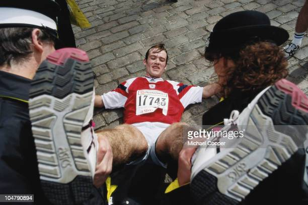 Competitor Mark Higgins recieves medical attention for cramp and exhaustion from St John's Ambulance personnel during the Nutrasweet London Marathon...
