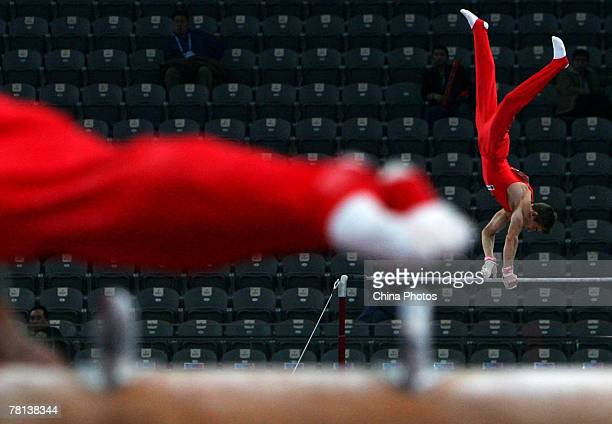 """Competitor performs on the horizontal bar during the men's qualification competition of the """"Good Luck Beijing"""" Gymnastics International Invitational..."""