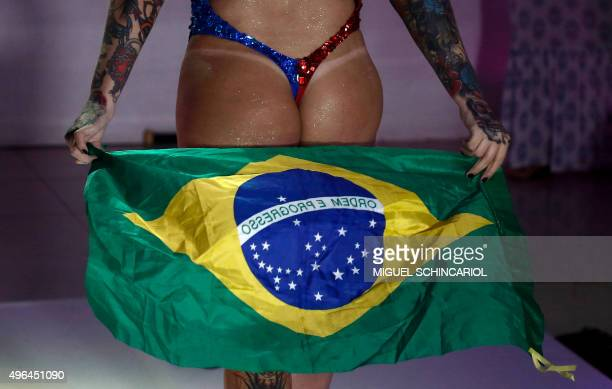 A competitor poses on the catwalk with the Brazilian national flag during the Miss Bumbum Brazil 2015 pageant in Sao Paulo Brazil on November 9 2015...