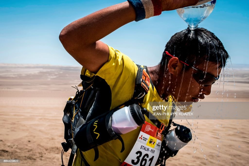 A competitor pours water on his head as he takes part in the fourth stage of the first edition of the Marathon des Sables Peru between Ocucaje and Barlovento (68,4 km) on December 1, 2017, in the Ica Desert in Peru. The 250km-race is divided into six stages through the Ica Desert at a free pace and in self-sufficiency conditions from November 28 to December 4, 2017. /