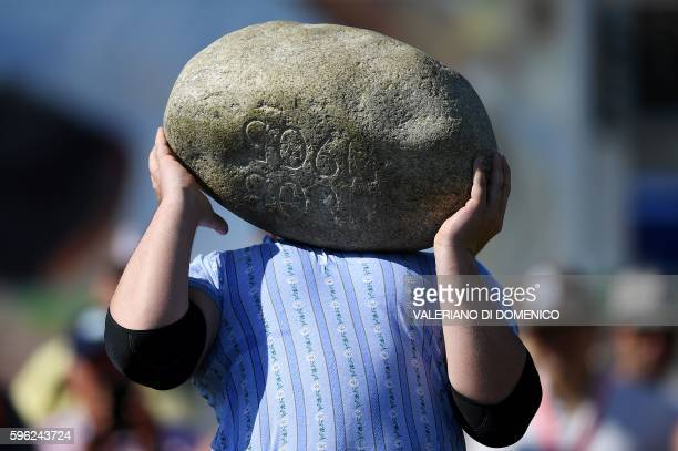 A competitor prepares to throw the 835kg Unspunnen stone during the first day of the Federal Alpine Wrestling Festival on August 27 2016 in Payerne...