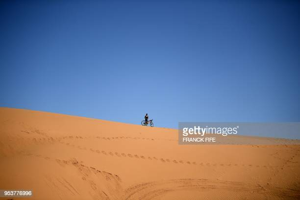 TOPSHOT A competitor rides a bike during Stage 4 of the 13th edition of the Titan Desert 2018 mountain biking race between Boumalne Dades and...