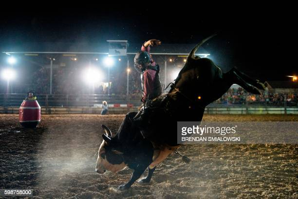 TOPSHOT A competitor rides a bull during a rodeo at the Shenandoah County Fair September 2 2016 in Woodstock Virginia / AFP PHOTO / Brendan Smialowski