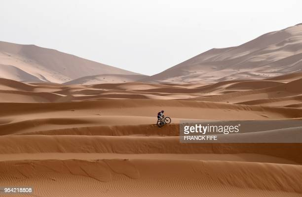 TOPSHOT A competitor rides his bike along a sand dune during Stage 5 of the 13th edition of Titan Desert 2018 mountain biking race around Merzouga in...