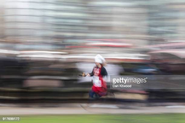 A competitor runs a lap during the annual Parliamentary Pancake Race in Victoria Tower Gardens on Shrove Tuesday on February 13 2018 in London...