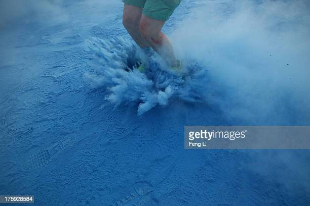 A competitor runs through the blue colour throw area during the Colour Run at the Beijing International Garden Expo park on August 10 2013 in Beijing...