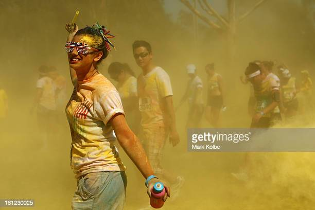 A competitor runs through the yellow colour throw during the Colour Run at Sydney Olympic Park on February 10 2013 in Sydney Australia