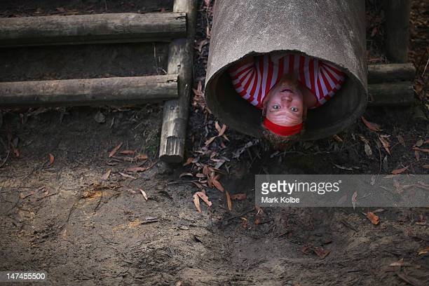 A competitor slides backwards down a concrete pipe in the Plumber's Crack obstacle as he competes in the Tough Bloke Challenge at the Cataract Scout...