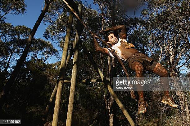 A competitor swings on a rope at the 'Donkey Kong' obstacle as he competes in the Tough Bloke Challenge at the Cataract Scout Park on June 30 2012 in...
