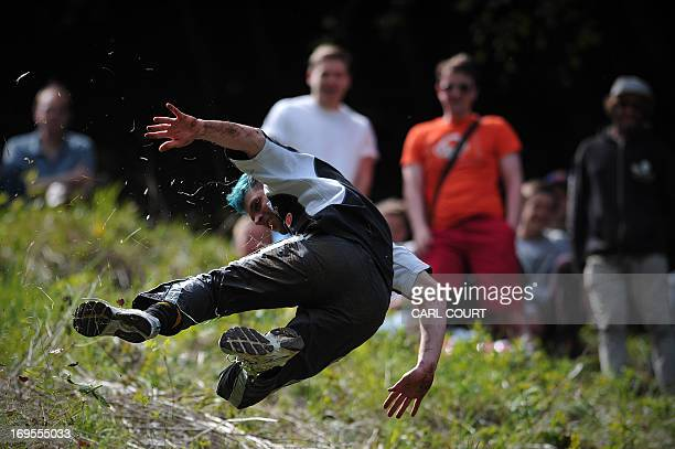 A competitor tumbles down Coopers Hill in pursuit of a fake foam round Double Gloucester cheese during the annual cheese rolling and wake near the...