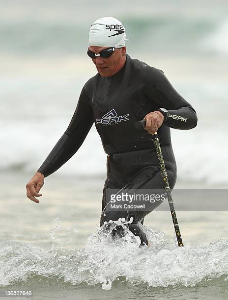 A competitor uses a walking stick to assist getting out of the water during the 2012 Pier to Pub on January 7 2012 in Lorne Australia