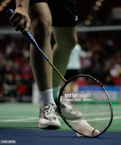 A competitor uses their racket to pick up a shuttle cock