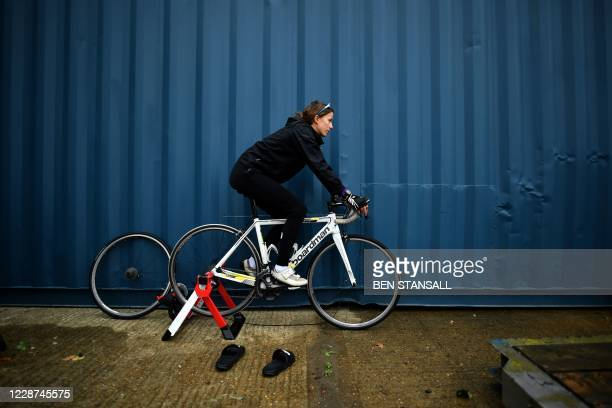 Competitor warms up on a trainer as she prepares to compete in the 44th Wigmore CC Hollingbourne Hill Climb, on the north downs in south-east England...