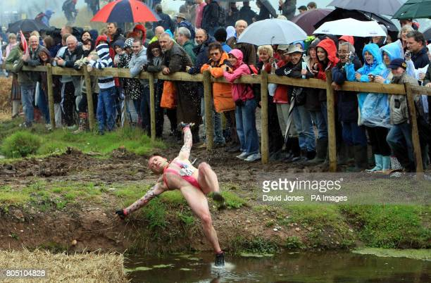 A competitor wearing a mankini performs falls into the 'Battle of the Somme' obstacle in the Nettle Warrior competition near Wolverhampton