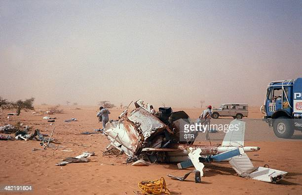 Competitors and officials search near the remains of the helicopter of the ParisDakar rally organizer Frenchman Thierry Sabine after it crashed 14...