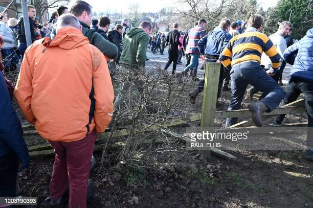Competitors and sepectators trample over a fence as they follow the action during the annual Royal Shrovetide Football Match between the the Up'ards...