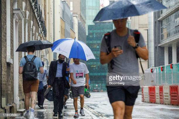 Competitors and supporters make their way in the rain to the start of the Standard Chartered City Race in the City of London, U.K., on Tuesday, July...