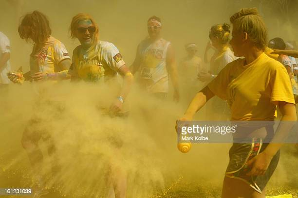 Competitors are covered in yellow powder as they run through the yellow colour throw during the Colour Run at Sydney Olympic Park on February 10 2013...