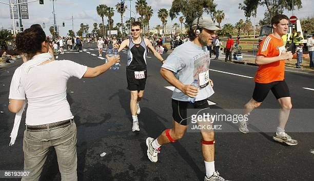 Competitors are given water bottles during the 2009 Tel Aviv Marathon on April 24 2009 in Tel Aviv After a 15year hiatus the Tel Aviv Marathon is...