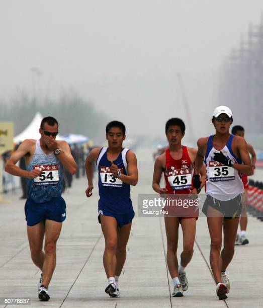 Competitors are shrouded with smog as they take part in the men's 50 km walk race during the 2008 BBMG IAAF Race Walking Challenge around the...