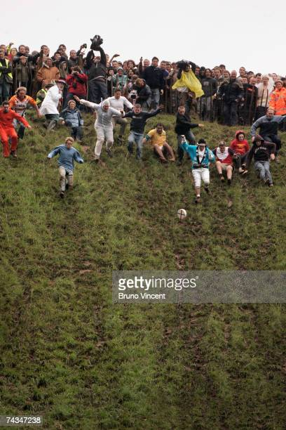Competitors begin the race down Coopers Hill to chase a cheese during the Cheese rolling event on May 28 2007 in Brockworth England The annual...