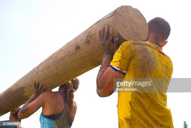 5K competitors carrying log to convey team work.