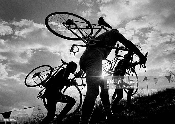 Competitors carrying their bikes uphill in silhouette against a dramatic sky and sunset during the World Cyclo-Cross Championships at Crystal Palace...