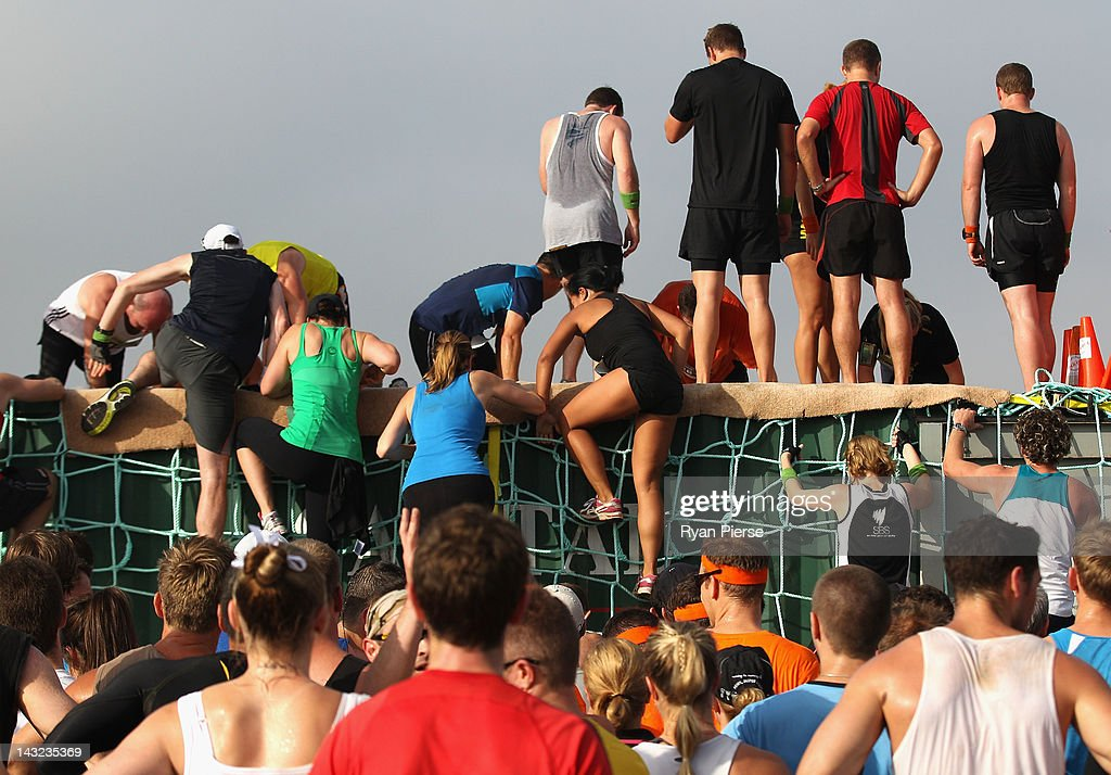 Competitors climb over the rope wall during the 2012 Men's Health Urbanathlon on April 22, 2012 in Sydney, Australia.