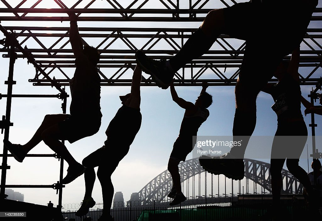 Competitors climb the Monkey Bars in front of the Sydney Harbour Bridge during the 2012 Men's Health Urbanathlon on April 22, 2012 in Sydney, Australia.