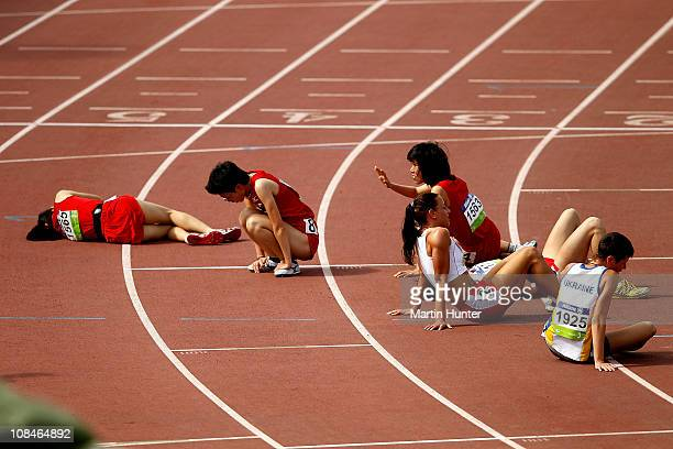 Competitors collapse on the finish line after the Women's 1500m T20 final during day seven of the IPC Athletics Championships at QE II Park on...