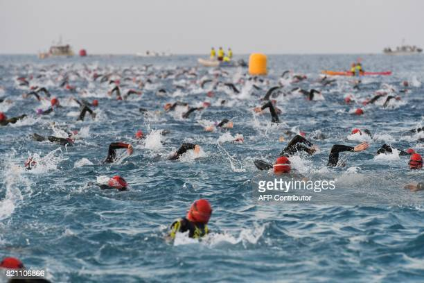 Competitors compete in the swimming race of the 13th Ironman thriathlon in Nice on July 23, 2017. / AFP PHOTO / YANN COATSALIOU