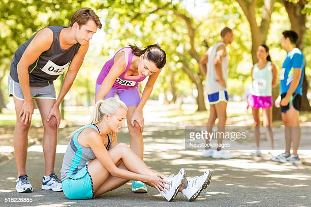 Competitors Consoling Marathon Runner Suffering From Twisted Ankle