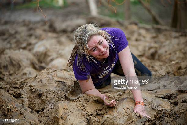 Competitors crawl in mud to avoid being electrocuted by dangling electric wires while challenging in Tough Mudder endurance race in HenleyonThames...
