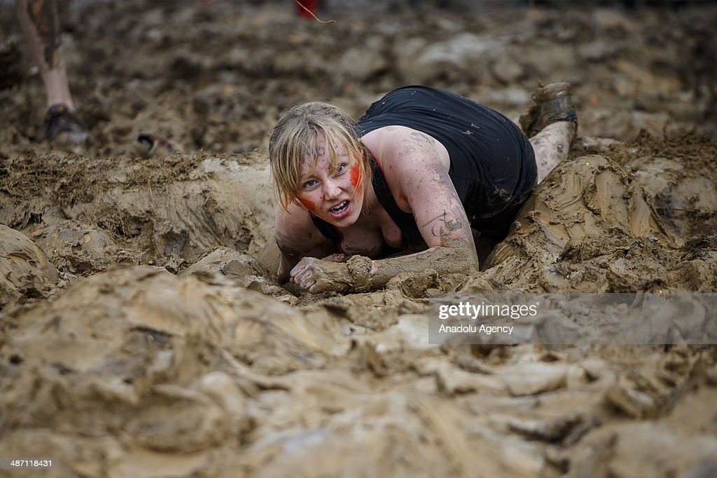 Competitors crawl in mud to avoid being electrocuted by dangling electric wires while challenging in Tough Mudder endurance race in Henley-on-Thames, England on 27 April, 2014. Competitors run a 19km course, designed by British Special Forces to test competitors' strength, stamina, mental grit, and camaraderie with mud and obstacles that play on common human fears, such as fire, water, electricity and heights.