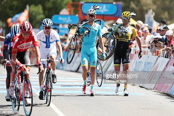 Competitors cross the finish line after a major crash just before the finish line during Stage 4 of the 2015 Santos Tour Down Under on January 23,...