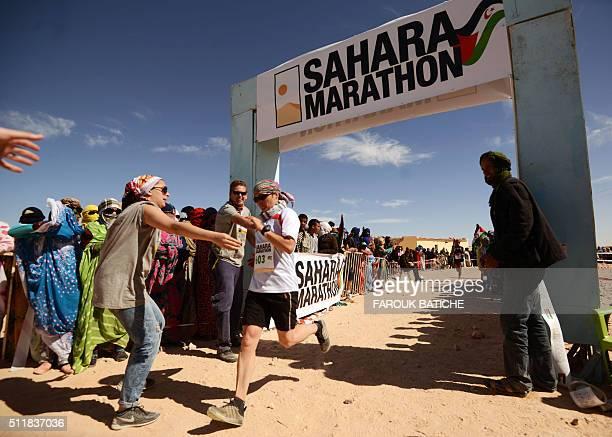 Competitors cross the finish line of the 16th Sahara Marathon on February 23 2016 at the Saharawi refugee camp of Smara in Algeria's Tindouf province...