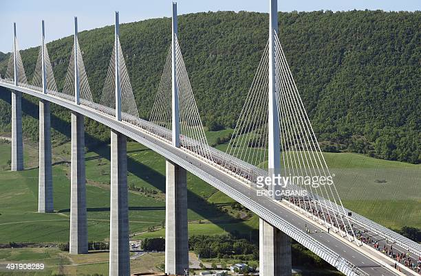 Competitors cross the Millau bridge as they take part in the 'Viaduc de Millau' race a 237 kilometers long race on May 18 2014 in Millau southern...