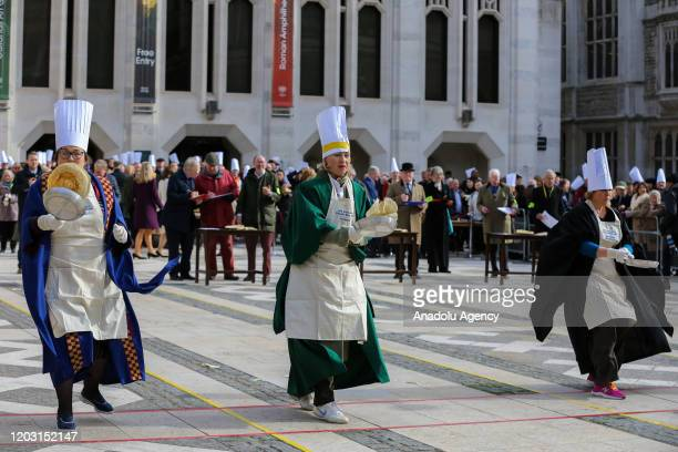 Competitors flip pancakes during the annual InterLivery Pancake Race on Shrove Tuesday at The Guildhall in London United Kingdom on February 25 2020...