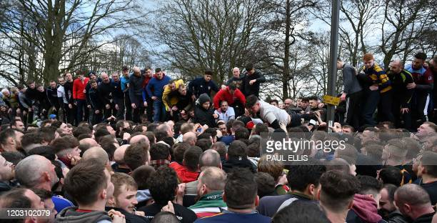 Competitors from the opposing teams the Up'ards and the Down'ards compete for the ball during the annual Royal Shrovetide Football Match in Ashbourne...