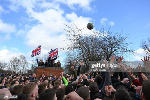 TOPSHOT Competitors from the opposing teams the Up'ards and the Down'ards reach for the ball at the start of the annual Royal Shrovetide Football...