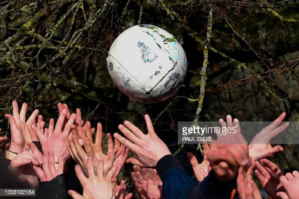 TOPSHOT Competitors from the opposing teams the Up'ards and the Down'ards reach for the ball during the annual Royal Shrovetide Football Match in...