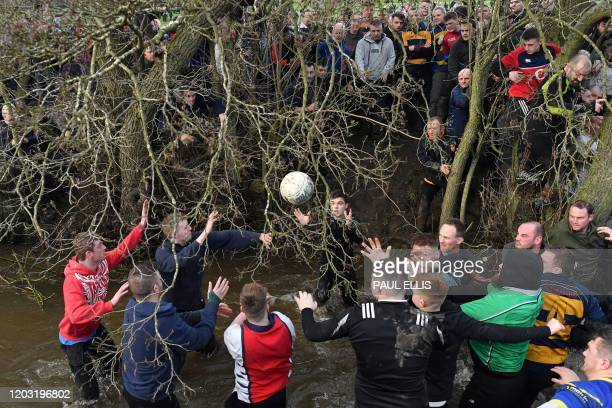 Competitors from the opposing teams the Up'ards and the Down'ards reach for the ball during the annual Royal Shrovetide Football Match in Ashbourne...