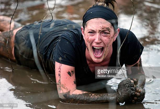 Competitors go through the Electric Eel where dangling wires give off electronic shocks during a Tough Mudder event held at the Seneca Hunt Club on...