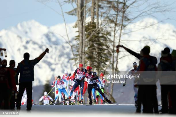 Competitors head towards a feed station as they compete in The Men's 50km Mass Start Free on Day 16 of the Sochi 2014 Winter Olympics at Laura...