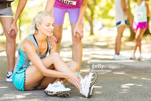 Competitors Helping Marathon Runner Suffering From Ankle Pain